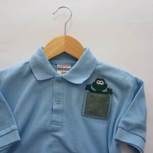 hellblaues Polohemd für Kinder mit Tasche und Frosch-Stickerei